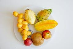 Platta med nya tropiska frukter på vit bakgrund Arkivfoton