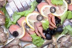 Platta med olika fiskläckerheter som isoleras på vit backgroun Royaltyfri Foto