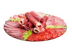 Platta med olika köttläckerheter som isoleras på vit backgroun Royaltyfri Bild
