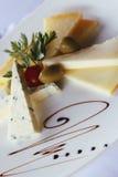 Platta med ostskivor och oliv Arkivfoto
