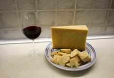 Platta med parmigianaregianoost och rött vin arkivfoto