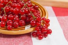 Platta med redcurrantbär på en tabell Arkivfoto