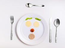 Platta med roliga emoticons som göras från mat med bestick på vit Royaltyfri Fotografi