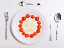 Platta med roliga emoticons som göras från mat med bestick på vit Arkivbild