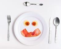 Platta med roliga emoticons som göras från mat med bestick på vit Royaltyfria Bilder