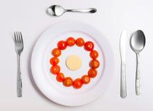Platta med roliga emoticons som göras från mat med bestick på vit Royaltyfri Bild