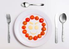 Platta med roliga emoticons som göras från mat med bestick på vit Fotografering för Bildbyråer