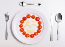 Platta med roliga emoticons som göras från mat med bestick på vit Arkivfoto