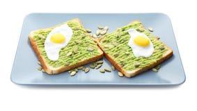 Platta med rostade bröd, avokadodeg och stekte ägg som isoleras royaltyfri fotografi