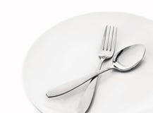 Platta med skeden och gaffeln arkivfoton