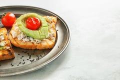 Platta med smakligt rostat bröd på ljus bakgrund arkivbild