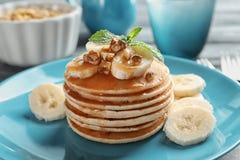 Platta med smaskiga bananpannkakor på köksbordet, Royaltyfria Foton