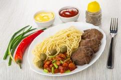 Platta med spagetti, kotletten, bönor, löken och oliv, ketchup, majonnäs, pepparshaker, chilipeppar, gaffel på tabellen royaltyfri fotografi