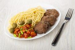 Platta med spagetti, kotletten, bönor, salladslöken och oliv, gaffel på tabellen arkivbilder
