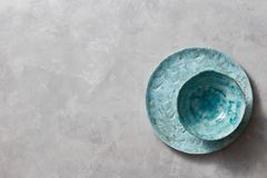 Platta och bunke för traditionell souvenirlera handgjord färgrik på en grå konkret bakgrund med stället under text Lekmanna- läge royaltyfria bilder