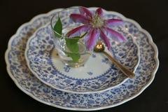 Platta och en blomma och ett exponeringsglas Arkivfoto