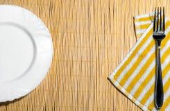 Platta och gaffel p? en servett p? tabellen arkivbilder