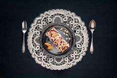 Platta, sked och gaffel för metall antik, på en gammal servett på en svart bakgrund arkivfoton