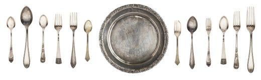 Platta, sked och gaffel för tappningmetall som antik isoleras på en vit bakgrund arkivfoto