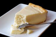 Platta till bakad ostkaka med kakan på gaffel på den vita keramiska plattan arkivfoto