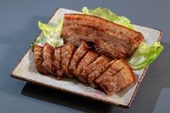Plattan av bacon för Hakkadiskpeppar med grönsallat på grå färger drar tillbaka Royaltyfri Bild