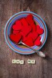 Plattan av röda hjärtor med text äter mycket mig Arkivbilder