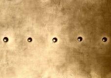 Plattan för metall för Grungeguldbrunt nitar skruvbakgrundstextur Royaltyfria Foton