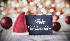 Plattan kalligrafi Frohe Weihnachten betyder glad jul, Santa Claus Hat royaltyfri fotografi