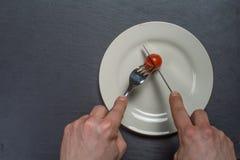 Plattan med en Tomate cutten vid cuttlery Fotografering för Bildbyråer