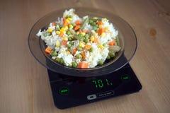 Plattan med löneförhöjning och grönsaker på kök graderar closeupen Royaltyfri Fotografi