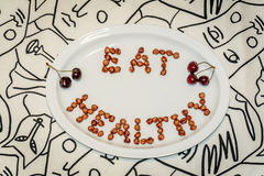 Plattan med ord äter sunt som göras av körsbärsröda kärnor Arkivfoton