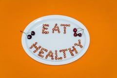 Plattan med ord äter sunt som göras av körsbärsröda kärnor på orange lodisar Arkivfoto