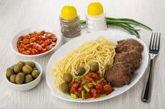 Plattan med spagetti, kotletten, bönor, lök och oliv, pepprar, saltar, bunkar med bönor, oliv, gaffel på tabellen arkivfoton