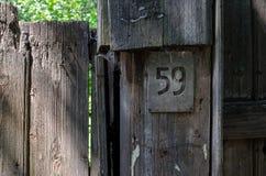 Plattan nummer 59 på ett gammalt trästaket Royaltyfri Foto