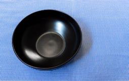 Plattar till den keramiska bunken för tomt svart sken på blått bakgrund Arkivbild