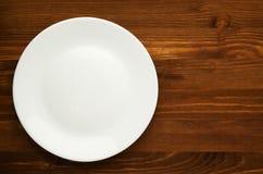 Platte auf einem hölzernen Hintergrund Draufsicht der Platte Kopieren Sie Platz weiß stockbild