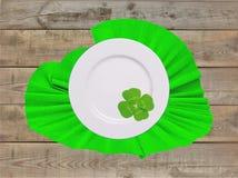 Platte auf grüner Serviette mit Kleeblatt für Tag St. Patricks Stockbilder