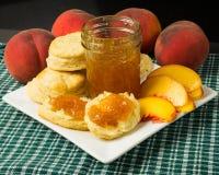 Platte der Biskuite mit Pfirsichen und Pfirsich blockieren Stockbilder