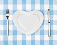 Platte in der Form des Inneren, des Tabellenmessers und der Gabel auf blauer Tischdecke Stockbild