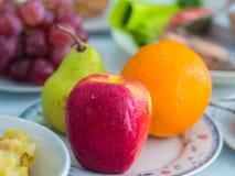 Platte des Apfels, der Orange und der Birne Stockfoto