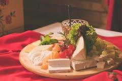 Platte des Käsesatzes in einem Holztisch Stockbilder