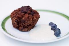 Platte des Schokoladenmuffins, der Blaubeeren und der Sojabohnenölcreme Stockfotografie