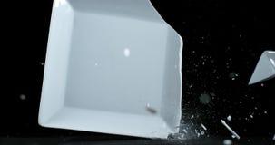 Platte, die auf schwarzem Hintergrund fällt und explodiert, stock video