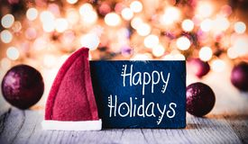 Platte, Kalligraphie frohe Feiertage, Santa Hat, purpurroter Ball stockfoto