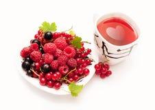 Platte mit Beeren und einer Schale rotem Tee Stockfotos