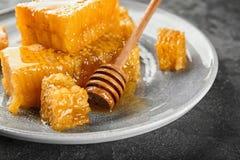 Platte mit Bienenwaben und hölzernem Schöpflöffel Stockbilder