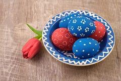 Platte mit blauen und roten Ostereiern und Tulpenblume auf hölzernem t Lizenzfreies Stockbild