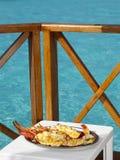 Platte mit dem gebackenen Hummer auf einem blauen Hintergrund des Meeres Lizenzfreie Stockfotos