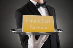 Platte mit dem Service der Text-ersten Klasse an Bord Lizenzfreies Stockbild