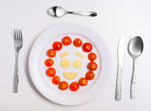 Platte mit den lustigen Emoticons gemacht vom Lebensmittel mit Tischbesteck auf Weiß Stockfotografie